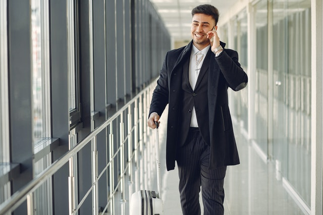 Businessman walking through an airport terminal while talking on his phone