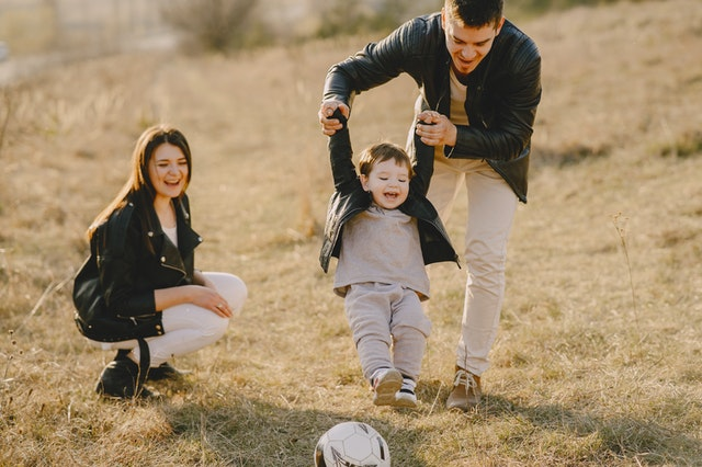Happy family playing with their young child.