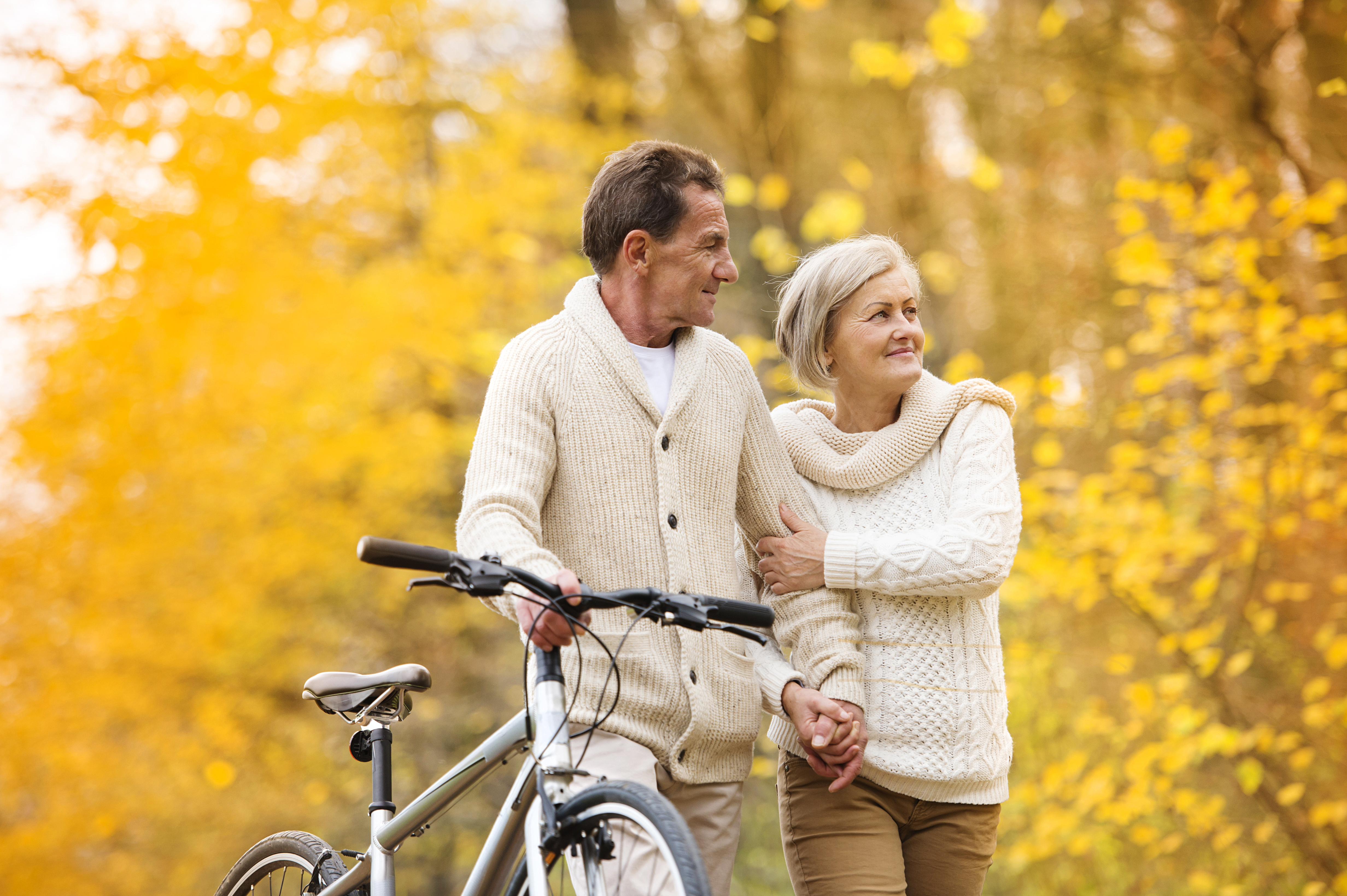 Elderly couple walking through a fall forest with a bicycle.
